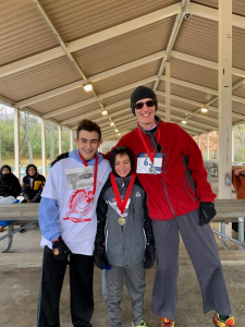 three students with medals from turkey trot