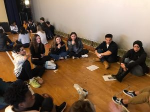 Students sitting in a circle sharing experiences.