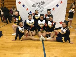 Seven cheerleaders posing for a picture in a gym.
