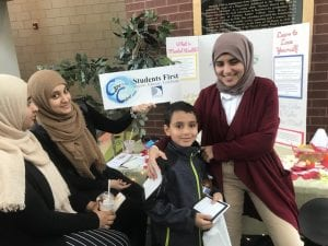 Two high school students sharing healthy living information with an elementary student.