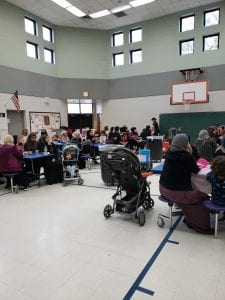 Families sitting in the Henry Ford Elementary cafeteria participating in Mother's Day breakfast.