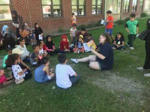 Students sitting on the grass with a teacher listening to her read a book.