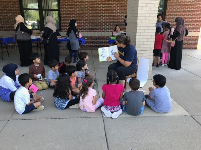 Teacher reading a book to a group of students sitting on the ground.