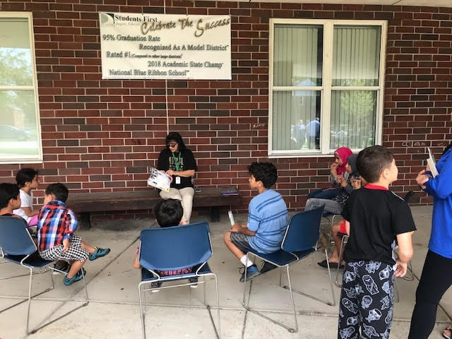 Teacher sitting on a bench reading to students.