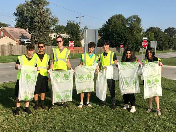 Seven high school Interact students standing on the Telegraph median holding MDot clean up bags.