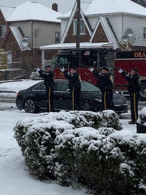 4 Veterans engage in the Honor Guard Salute.  Snow is falling.