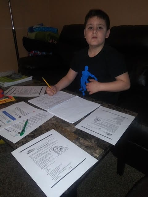 Student holding a pencil, seated at a table completing schoolwork.